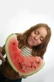 Donna felice che gode mangiando una fetta di anguria Immagini Stock