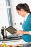 Donna felice che guarda la lettura della cucina della compressa di ricetta Fotografie Stock Libere da Diritti