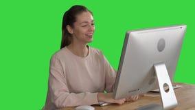 Donna felice che ha una video chiamata che si siede davanti al suo computer su uno schermo verde, chiave di intensità archivi video