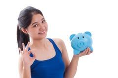 Donna felice che indica al porcellino salvadanaio con la mostra dell'approvazione Immagine Stock