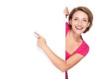 Donna felice che indica con il suo dito sull'insegna fotografie stock