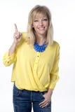 Donna felice che indica su con il suo dito Fotografia Stock