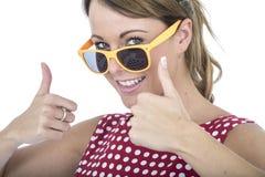 Donna felice che indossa i vetri di Sun gialli che danno i pollici su Fotografie Stock Libere da Diritti