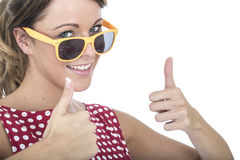 Donna felice che indossa i vetri di Sun gialli che danno i pollici su Immagini Stock