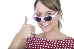 Donna felice che indossa i vetri di Sun rosa che danno i pollici su Immagine Stock Libera da Diritti