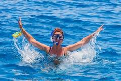 Donna felice che indossa una maschera nel mare, con una macchina fotografica Fotografia Stock