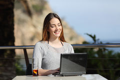 Donna felice che lavora con il suo computer portatile in un terrazzo dell'hotel Immagine Stock