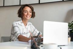 Donna felice che lavora dalla tavola con il computer portatile Fotografie Stock Libere da Diritti