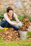 Donna felice che mette l'iarda asciutta del secchio delle foglie Fotografie Stock