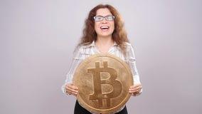 Donna felice che mostra la grande moneta di Bitcoin Concetto virtuale dei soldi Cryptocurrency video d archivio