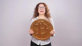 Donna felice che mostra la grande moneta di Bitcoin Concetto virtuale dei soldi Cryptocurrency archivi video