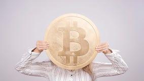 Donna felice che mostra la grande moneta di Bitcoin Concetto virtuale dei soldi Cryptocurrency stock footage