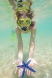 Donna felice che mostra le stelle marine fotografia stock