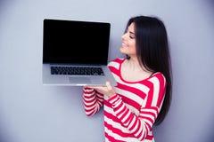 Donna felice che mostra lo schermo in bianco del computer portatile Fotografia Stock Libera da Diritti