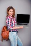 Donna felice che mostra lo schermo in bianco del computer portatile Fotografie Stock Libere da Diritti