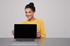 Donna felice che mostra lo schermo nero in bianco del comuter Immagine Stock