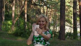 Donna felice che ondeggia sulla video chiacchierata con lo smartphone in foresta all'aperto video d archivio