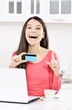 Donna felice che osserva indietro con il computer portatile immagini stock