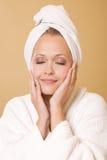 Donna felice che ottiene il tovagliolo da portare di trattamento di bellezza immagini stock