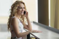 Donna felice che parla con il telefono delle cellule mentre sedendosi nella caffetteria durante la prima colazione di mattina Immagini Stock
