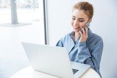 Donna felice che parla sul telefono cellulare e che per mezzo del computer portatile Fotografia Stock Libera da Diritti