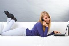 Donna felice che parla sul telefono cellulare e che per mezzo del computer portatile che si trova sul sofà, tecnologia moderna Fotografie Stock