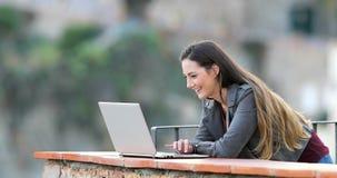 Donna felice che passa in rassegna contenuto online su un computer portatile video d archivio