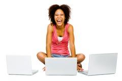 Donna felice che per mezzo dei computer portatili Fotografia Stock