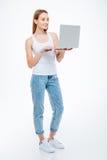 Donna felice che per mezzo del computer portatile Immagine Stock Libera da Diritti