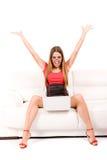 Donna felice che per mezzo del computer portatile Fotografia Stock