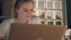 Donna felice che per mezzo del computer portatile archivi video