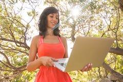 Donna felice che per mezzo del computer portatile al giardino Immagini Stock Libere da Diritti