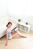 Donna felice che per mezzo del pc della compressa sul sofà Fotografia Stock
