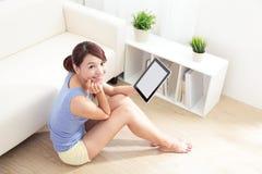 Donna felice che per mezzo del pc della compressa sul sofà Fotografia Stock Libera da Diritti