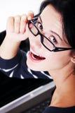 Donna felice che per mezzo del suo computer portatile Fotografie Stock