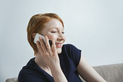 Donna felice che per mezzo del telefono cellulare Fotografie Stock