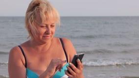 Donna felice che per mezzo del telefono per comunicare su Internet contro il contesto delle onde del mare stock footage