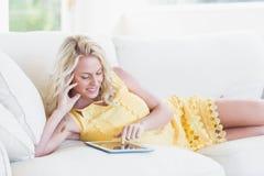 Donna felice che per mezzo della compressa sul sofà Fotografia Stock Libera da Diritti