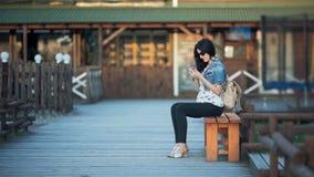 Donna felice che per mezzo dello smartphone al caffè all'aperto sul tramonto stock footage