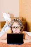 Donna felice che per mezzo di un computer portatile immagine stock libera da diritti