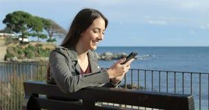 Donna felice che per mezzo di uno Smart Phone sulla spiaggia archivi video