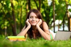 Donna felice che pone sull'erba Immagini Stock