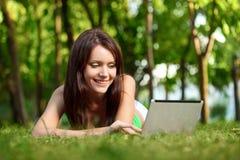 Donna felice che pone sull'erba con il computer portatile Fotografia Stock