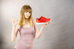 Donna felice che presenta ad istruttori degli abiti sportivi le scarpe Fotografia Stock