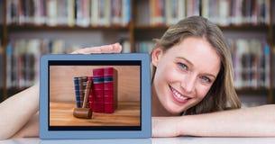 Donna felice che presenta compressa con il mucchio dei libri mentre sedendosi allo scrittorio in biblioteca Fotografia Stock