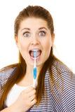 Donna felice che pulisce i suoi denti con lo spazzolino da denti Fotografia Stock