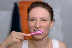 Donna felice che pulisce i suoi denti con uno spazzolino da denti Fotografie Stock Libere da Diritti