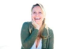Donna felice che ride con la mano sulla guancica immagini stock
