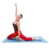 Donna felice che risolve sulla stuoia blu di esercizio immagini stock