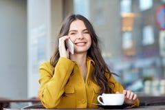 Donna felice che rivolge allo smartphone al caffè della città Immagini Stock Libere da Diritti